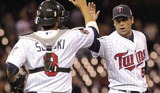 Minnesota Twins relief pitcher Anthony Swarzak (51) is congratulated by teammate Kurt Suzuki (8) after they beat the Kansas City Royals 10-1 in a baseball game, Friday, April 11, 2014, in Minneapolis. AP Photo/Paul Battaglia)