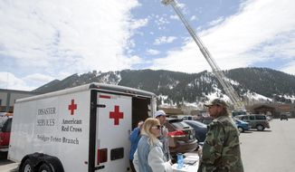John Friedrich and Jane Koas talk with the American Red Cross Thursday, April 10, 2014 after being evacuated from their home on Budge Drive in Jackson, Wyo. Significant earth movement in the East Gros Ventre Butte hillside, already responsible for a broken water pipe and some property damage, prompted officials to order the evacuation on Wednesday evening. Jackson Hole Fire/EMS uses a ladder truck to watch the area in question, providing safety watch for geologists and law enforcement working on the slope. (AP Photo/Jackson Hole News and Guide, Price Chambers)