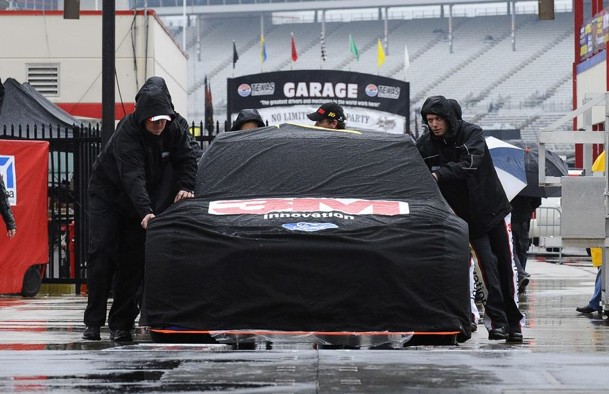The crew for Greg Biffle roll their covered car during setups for the NASCAR Sprint Cup Series auto race at Texas Motor Speedway in Fort Worth, Texas, Sunday, April 6, 2014. (AP Photo/Ralph Lauer)