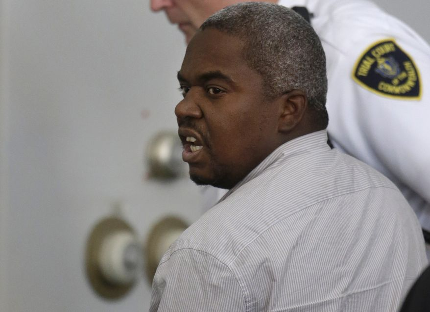 Ernest Wallace, of Miramar, Fla., mouths words to people sitting in Attleboro District Court, in Attleboro, Mass., as he is escorted from the court room after pleading not guilty during his arraignment, Monday, July 8, 2013. Wallace is facing an accessory to murder charge in the case involving former New England Patriots tight end Aaron Hernandez and has been ordered held without bail. (AP Photo/Steven Senne, Pool)