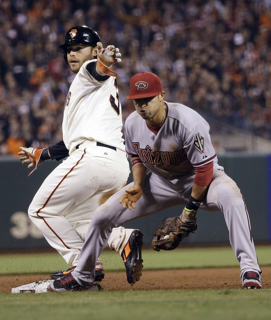 San Francisco Giants' Brandon Crawford, left, is forced out at third base by Arizona Diamondbacks third baseman Martin Prado after a bunt by Ryan Vogelsong during the fourth inning of a baseball game on Thursday, April 10, 2014, in San Francisco. (AP Photo/Marcio Jose Sanchez)