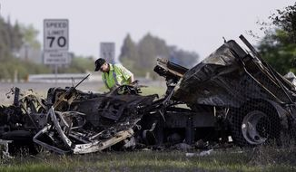 A worker looks over the demolished cab of FedEx truck that crashed into a tour bus on Interstate 5 Thursday in Orland, Calif., Friday, April 11, 2014. At least ten people were killed and dozens injured in the fiery crash between the truck and a bus carrying high school students on a visit to a Northern California College. (AP Photo/Jeff Chiu)