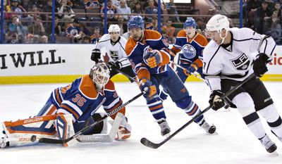Los Angeles Kings' Jeff Carter (77) is stopped by Edmonton Oilers goalie Viktor Fasth (35) as Jarret Stoll (28), Mark Fraser (5) and Ryan Nugent-Hopkins (93) look for the rebound during first-period NHL hockey game action in Edmonton, Alberta, Thursday, April 10, 2014. (AP Photo/The Canadian Press, Jason Franson)