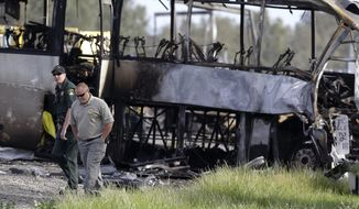 Glenn County Sheriff's officers walk past the remains of a tour bus that was struck by a FedEx truck on Interstate 5 Thursday in Orland, Calif., Friday, April 11, 2014. At least ten people were killed and dozens injured in the fiery crash between the truck and a bus carrying high school students on a visit to a Northern California College. (AP Photo/Jeff Chiu)