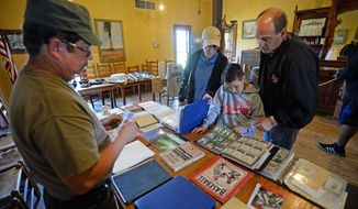 ADVANCE FOR USE MONDAY APRIL 14, 2014, AND THEREAFTER- In this April 5, 2014 photo, Don Smart, left, shows his baseball relics to Bryan Klutts, Evan Klutts, 8, and Sharon Klutts during a vintage baseball exhibit in Gladys City, Texas. (AP Photo/The Beaumont Enterprise, Guiseppe Barranco)
