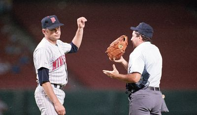 FILE - In this Aug. 3, 1987 file photo, Minnesota Twins pitcher Joe Niekro tosses his glove to home plate umpire Tim Tscida after the umpire stopped the game between the Twins and Angels in Anaheim, Calif.  Niekro was thrown from the game after the umpires reportly found an emery board on Niekro and called him for defacing the baseball. (AP Photo/Lennox Mclendon, File)