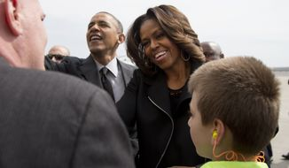 President Barack Obama and first lady Michelle Obama greet people on the tarmac as they arrive on Air Force One at John F. Kennedy International Airport in New York, Friday, April 11, 2014, as they travel to the Al Sharpton's National Action Network's 16th Annual Convention. (AP Photo/Carolyn Kaster)