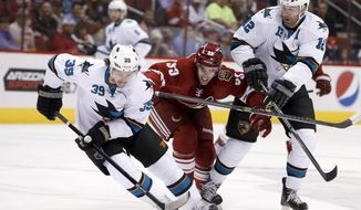 San Jose Sharks' Logan Couture, left, controls the puck as Phoenix Coyotes' Brandon Gormley (33) runs into Shark's Patrick Marleau (12) during the first period of an NHL hockey game on Saturday, April 12, 2014, in Glendale, Ariz. (AP Photo/Ross D. Franklin)