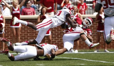 Oklahoma running back Daniel Brooks (34) is tackled by Oklahoma White's Londell Taylor (31) during their annual spring NCAA college football game in Norman, Okla., Saturday, April 12, 2014. (AP Photo/Alonzo Adams)