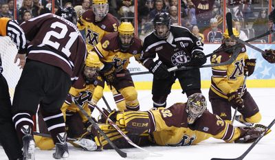 Minnesota's Adam Wilcox, bottom right, reaches as Union's Mike Vecchione, left, shoots the puck for a goal during the first period of an NCAA men's college hockey Frozen Four tournament game on Saturday, April 12, 2014, in Philadelphia. (AP Photo/Chris Szagola)