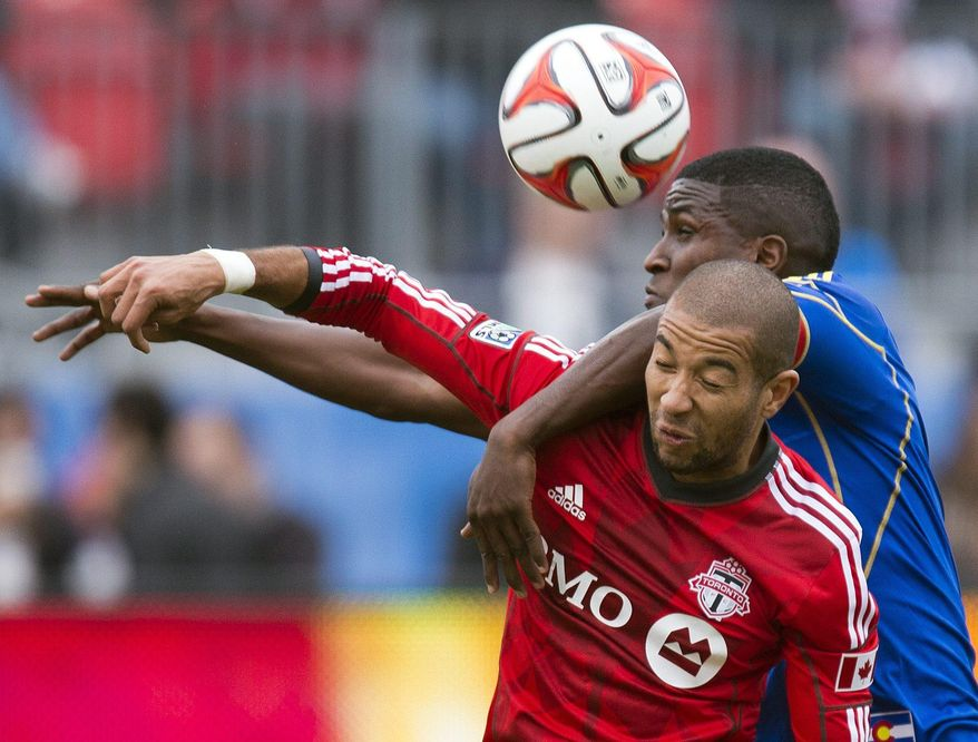 Toronto FC's defender Justin Morrow, front, and Colorado Rapids forward Edson Buddle battle for a header during first half MLS action in Toronto on Saturday, April 12, 2014. (AP Photo/The Canadian Press, Frank Gunn)