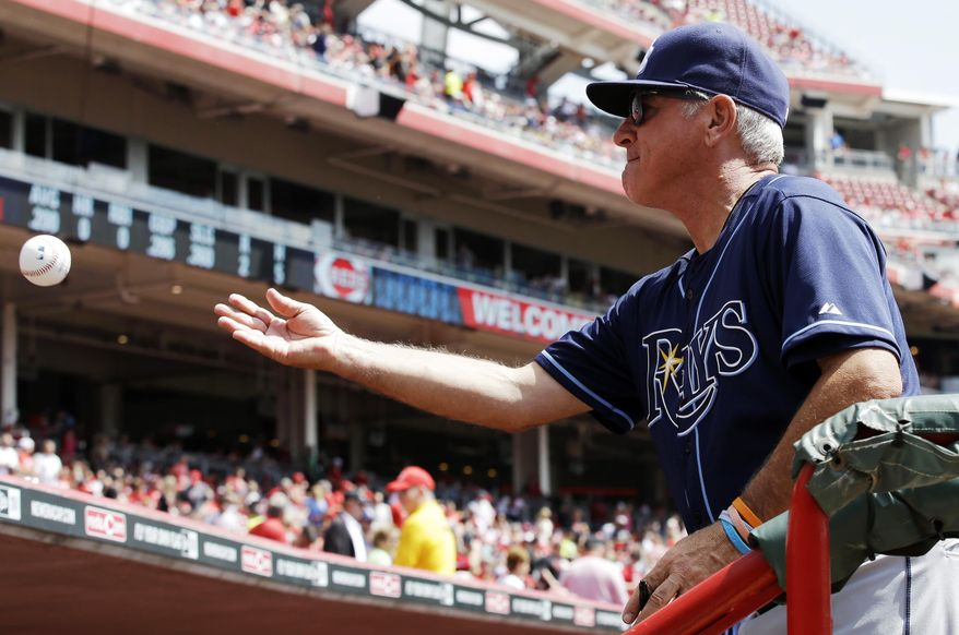 Tampa Bay Rays manager Joe Maddon tosses a ball back to a fan after autographing it prior to the start of a baseball game against the Cincinnati Reds, Saturday, April 12, 2014, in Cincinnati. (AP Photo/Al Behrman)