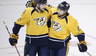 Nashville Predators forward Craig Smith (15) is congratulated by Mattias Ekholm (42), of Sweden, after Smith scored against the Chicago Blackhawks in the first period of an NHL hockey game Saturday, April 12, 2014, in Nashville, Tenn. (AP Photo/Mark Humphrey)