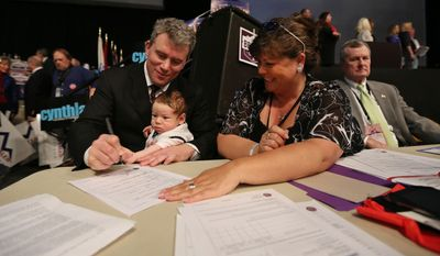 Colorado Secretary of State Scott Gessler holds his baby Eric as he signs his candidate acceptance of designation form as Lana Ford Warkocz, the secretary for the state Republican party looks on, at the state GOP Congress, in Boulder, Colo., Saturday April 12, 2014. Gessler made the ballot along with Mike Kopp, in hope of challenging Democratic Gov. John Hickenlooper this fall. (AP Photo/Brennan Linsley)