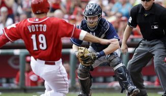 Tampa Bay Rays catcher Ryan Hanigan waits to tag out Cincinnati Reds' Joey Votto (19) at home in the fourth inning of a baseball game, Saturday, April 12, 2014, in Cincinnati. Votto was trying to score on a hit by Brandon Phillips. Umpire Clint Fagan watches. (AP Photo/Al Behrman)