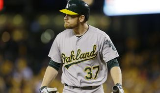 Oakland Athletics' Brandon Moss looks toward the mound after he struck out swinging against Seattle Mariners starting pitcher Felix Hernandez in the fourth inning of a baseball game, Friday, April 11, 2014, in Seattle. (AP Photo/Ted S. Warren)