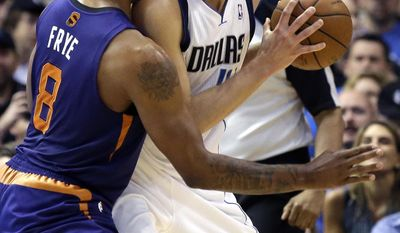 Dallas Mavericks forward Dirk Nowitzki, right, of Germany, get close defense from Phoenix Suns forward Channing Frye (8)  during the first half of an NBA basketball game on Saturday, April 12, 2014, in Dallas. (AP Photo/LM Otero)