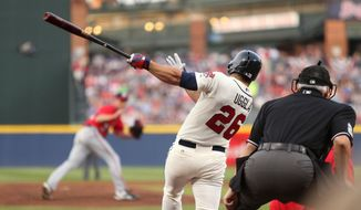 Atlanta Braves' Dan Uggla (26) hits a single to left field off Washington Nationals starting pitcher Taylor Jordan, left, in the first inning of a baseball game on Saturday, April 12, 2014, in Atlanta. (AP Photo/Jason Getz)