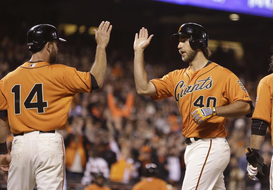 San Francisco Giants' Madison Bumgarner, right, is greeted by teammate Brandon Hicks, left, after hitting a grand slam off Colorado Rockies starting pitcher Jorge De La Rosa during the fourth inning of a baseball game Friday, April 11, 2014, in San Francisco. (AP Photo/Eric Risberg)