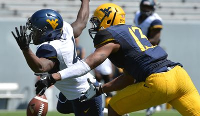 West Virginia's Wendell Smallwood (4) can't hold onto a pass while defended by Sean Williams (13) during spring NCAA college football game in Morgantown, W.Va., Saturday, April 12, 2014. (AP Photo/Craig Cunningham)