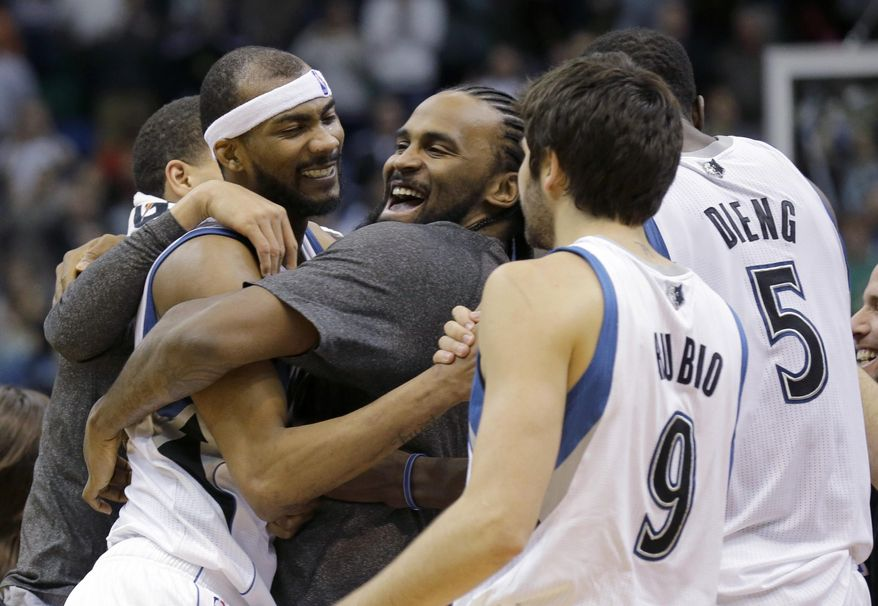 Minnesota Timberwolves forward Corey Brewer, left,  celebrates with teammates Ronny Turiaf, center, of France; Ricky Rubio (9), of Spain; and Gorgui Dieng (5) after the Timberwolves defeated the Houston Rockets 112-110 in an NBA basketball game in Minneapolis, Friday, April 11, 2014. (AP Photo/Ann Heisenfelt)