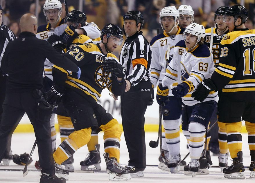 Buffalo Sabres' Tyler Ennis (63) reaches out as Boston Bruins' Daniel Paille (20) struggles to stand during the third period of an NHL hockey game in Boston, Saturday, April 12, 2014. Paille was helped from the ice after falling hard when he collided with the Sabres' Jake McCabe. The Bruins won 4-1. (AP Photo/Michael Dwyer)