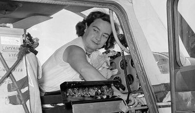 FILE - This photo made April 16, 1964, shows Jerrie Mock checking her extra gas tank cap just before taking off from Oakland Airport, in Oakland, California. Fifty years ago the 38-year-old Columbus, Ohio, housewife became the first woman to fly solo around the world. (AP Photo/Robert W. Klein)