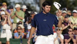 Bubba Watson tips his cap after putting on the 18th green during the third round of the Masters golf tournament Saturday, April 12, 2014, in Augusta, Ga. (AP Photo/Charlie Riedel)