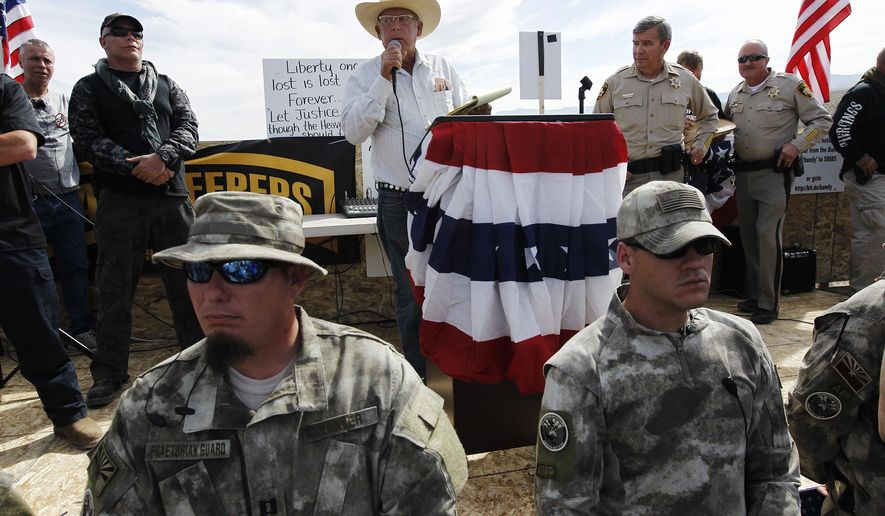 Rancher Cliven Bundy, middle, addresses his supporters along side Clark County Sheriff Doug Gillespie, right, on April 12, 2014. (AP Photo/Las Vegas Review-Journal, Jason Bean)