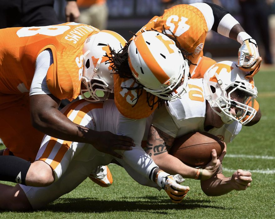 Tennessee quarterback Riley Ferguson (10) is stopped by linebackers A.J. Johnson (45) and Owen Williams (58) during the Orange and White game at Neyland Stadium in Knoxville, Tenn., Saturday, April 12, 2014. (AP Photo/Knoxville News Sentinel, Amy Smotherman Burgess)