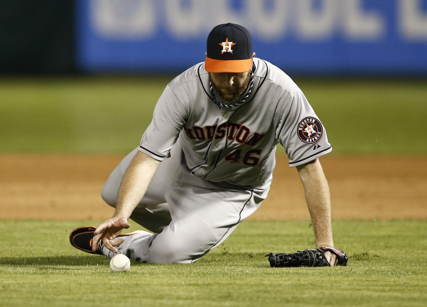 Houston Astros starting pitcher Scott Feldman scrambles for the ball on an infield hit by Texas Rangers' Leonys Martin during the fifth inning of a baseball game, Friday, April 11, 2014, in Arlington, Texas. (AP Photo/Jim Cowsert)
