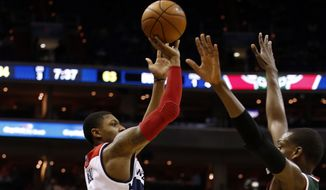 Washington Wizards guard Bradley Beal (3) shoots over Milwaukee Bucks forward Khris Middleton (22) during the second half of an NBA basketball game, Saturday, April 12, 2014, in Washington. Beal had 26 points. The Wizards won 104-91. (AP Photo/Alex Brandon)