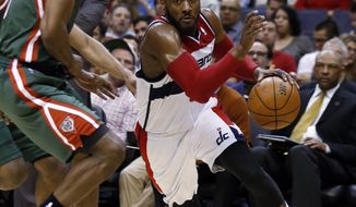 Washington Wizards guard John Wall drives past Milwaukee Bucks forward Chris Wright during the second half of an NBA basketball game, Saturday, April 12, 2014, in Washington. The Wizards won 104-91. (AP Photo/Alex Brandon)