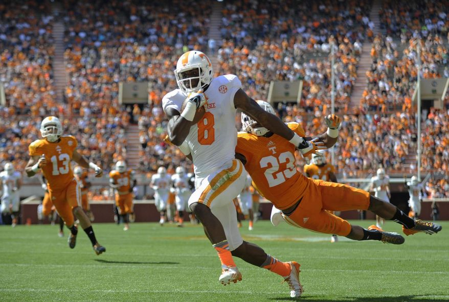 Tennessee wide receiver Marquez North (8) runs for a touchdown past Tennessee defensive back Cameron Sutton (23) during the first half of the Orange and White game at Neyland Stadium in Knoxville, Tenn., Saturday, April 12, 2014. (AP Photo/Knoxville News Sentinel, Adam Lau)