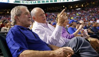 Former Texas Rangers President Nolan Ryan, right, shared the front row with former President George W. Bush as Ryan made his return, with his new team the Houston Astros, at the Globe Life Park in Arlington, Texas, on Friday, April 11, 2014. (AP Photo/The Dallas Morning News, Tom Fox)