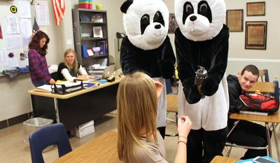 Derek Brown, left, and Joel Toppin catch Tjaden Kramer by surprise Wednesday, April 2, 2014, at Garner-Hayfield/Ventura, Iowa, High School as they present her an award while in panda costumes. Brown and Toppin are part of Random Acts of Coolness, a student led group that promotes kindness and respect. (AP photo/Globe Gazette, Ashley Miller)