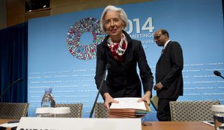 ** FILE ** International Monetary Fund (IMF) Managing Director Christine Lagarde accompanied by IMFC Chair and Singapore Finance Minister Tharman Shanmugaratnam, arrive for a news conference during the World Bank Group-International Monetary Fund Spring Meetings in Washington, Saturday, April 12, 2014. ( AP Photo/Jose Luis Magana)