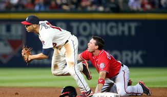 Washington Nationals' Ryan Zimmerman, right, reacts after being tagged out by Atlanta Braves shortstop Andrelton Simmons, left, at second base on a pickoff by Braves starting pitcher Alex Wood in the fifth inning of a baseball game on Saturday, April 12, 2014, in Atlanta. (AP Photo/Jason Getz)