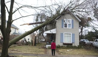 Eva, who did not want to give her last name, looks at the damage of a neighbors home after a storm in the village of Sparta, Mich., Sunday, April 13, 2014. A wave of severe thunderstorms has blown across the southern half of Michigan, knocking out power to at least 174,000 homes and businesses and shutting down parts of two interstate highways because of fallen power lines. (AP Photo/The Grand Rapids Press, Lauren Petracca) ALL LOCAL TV OUT; LOCAL TV INTERNET OUT