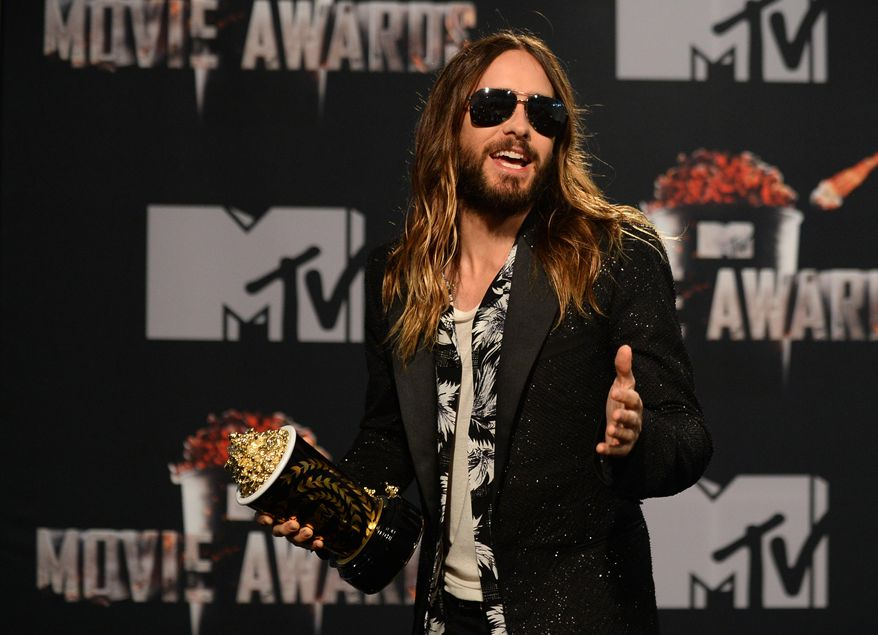 """Jared Leto poses in the press room with the award for Best On-Screen Transformation for """"Dallas Buyers Club"""" at the MTV Movie Awards on Sunday, April 13, 2014, at Nokia Theatre in Los Angeles. (Photo by Jordan Strauss/Invision/AP)"""