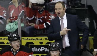 New Jersey Devils head coach Peter DeBoer, left,  directs his players during the third period of an NHL hockey game against the Calgary Flames in Newark, N.J., Monday, April 7, 2014. The Flames won 1-0. (AP Photo/Mel Evans)