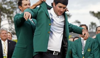 Defending Masters' champion Adam Scott, of Australia, helps Bubba Watson, right, with his green jacket after winning the Masters golf tournament Sunday, April 13, 2014, in Augusta, Ga.  (AP Photo/Matt Slocum)