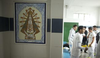"""Soccer players from the new team """"Papa Francisco,"""" or Pope Francis, get ready for a game in their locker room decorated with an image of Our Lady of Lujan, Argentina's Patron Saint in Lujan, Argentina, Saturday, April 12, 2014. The new semiprofessional team named their team in honor of the pontiff from Argentina. (AP Photo/Victor R. Caivano)"""