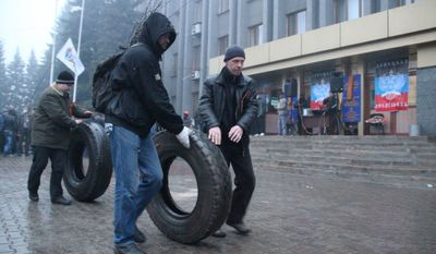 Pro-Russian activists roll tires to make barricades in front of the city government headquarters in Makeyevka, Ukraine on Sunday. (Associated Press)