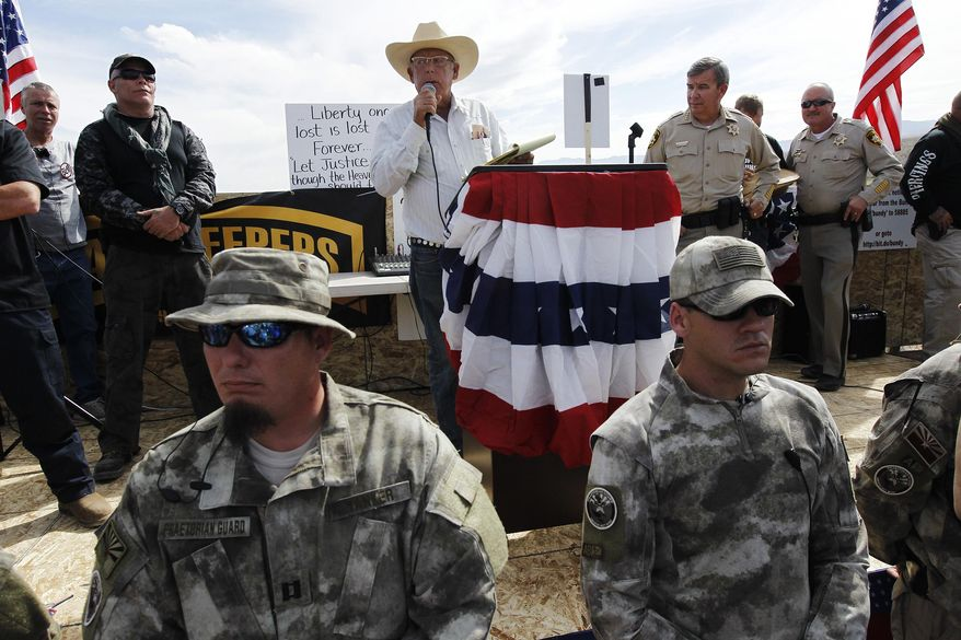 Rancher Cliven Bundy, middle, addresses his supporters along side Clark County Sheriff Doug Gillespie, right, on April 12, 2014. Bundy informed the public that the BLM has agreed to cease the roundup of his family's cattle.(AP Photo/Las Vegas Review-Journal, Jason Bean)