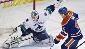 Vancouver Canucks' Jacob Markstrom (35) makes the save on Edmonton Oilers' Taylor Hall (4) during the second period of an NHL hockey game Saturday, April 12, 2014, in Edmonton, Alberta. (AP Photo/The Canadian Press, Jason Franson)