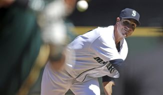 Seattle Mariners starting pitcher Chris Young throws against the Oakland Athletics in the first inning of a baseball game Sunday, April 13, 2014, in Seattle. (AP Photo/Elaine Thompson)