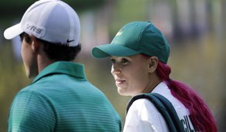 Rory McIlroy, of Northern Ireland, walks with his fiancee and tennis player Caroline Wozniacki after Wozniacki putted on the ninth hole during the par three competition at the Masters golf tournament Wednesday, April 9, 2014, in Augusta, Ga. (AP Photo/David J. Phillip)