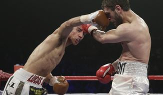 Jessie Vargas, left, reaches with a right to the face of Khabib Allakhverdiev, from Russia in their WBA-IBO junior welterweight title boxing fight Saturday, April 12, 2014, in Las Vegas. Vargas won the bout by unanimous decision. (AP Photo/Isaac Brekken)