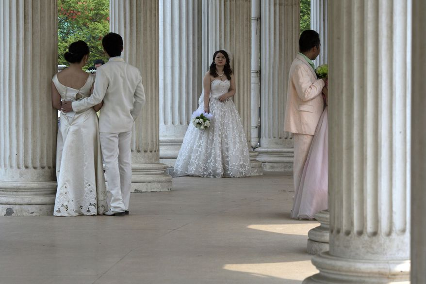 A bride waits for her groom as other couples pose for wedding photos at a park in Beijing, China, Sunday, April 13, 2014. (AP Photo/Ng Han Guan)